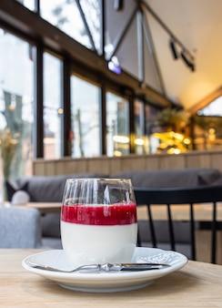 Pyszny włoski deser panna cotta z sosem jagodowym na drewnianym stole, powierzchnia wnętrza kawiarni