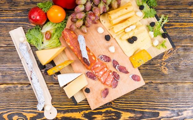Pyszny wybór różnych serów i pikantnej kiełbasy na desce serów z winogronami przyozdobionymi świeżymi jeżynami, oliwkami i papryką, widok z góry