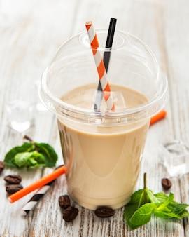 Pyszny zimny koktajl kawowy z mlekiem i miętą na białym drewnianym stole