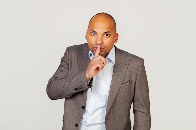 Pyta młody mężczyzna afroamerykanin biznesmen w kurtce, przyciskając palec wskazujący do ust