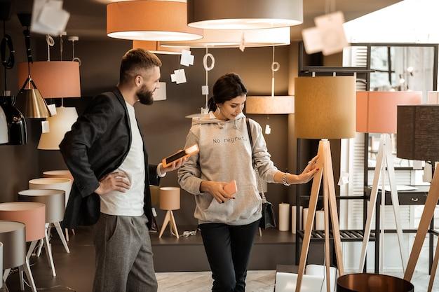 Pytający konsultant. zainteresowana kobieta dotyka mebli ustawionych w salonie, podczas gdy konsultant w kurtce stoi obok