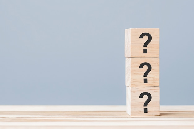 Pytania mark (?) na drewnianym sześcianowym bloku na stołowym tle. faq (często zadawane pytania), odpowiedzi, pytania i odpowiedzi, informacje, komunikacja i koncepcje przesłuchań