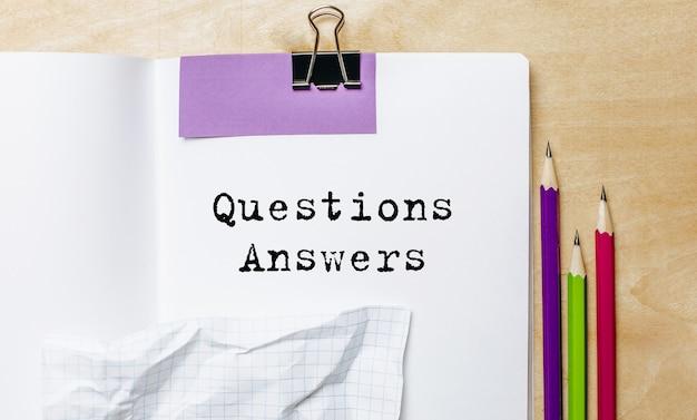 Pytania odpowiedzi tekst zapisany na papierze z ołówkami na biurku