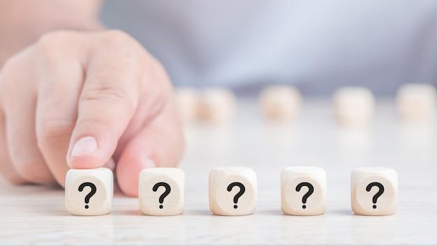 Pytania zaznaczaj słowa w drewnianych kostkach na tle stołu