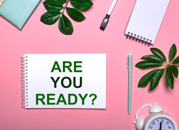 Pytanie jesteś gotowy jest napisane na zielono na białym notatniku na różowej ścianie otoczonej notatnikami, długopisami, białym budzikiem i zielonymi liśćmi. koncepcja edukacyjna