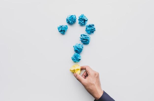 Pytanie lub myślenie pomysły pomysły z męskiej ręki trzymającej zmiętą piłkę papieru