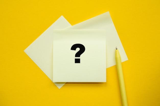 Pytanie - napis na żółtych naklejkach i papierze, żółty pan na żółtym tle.