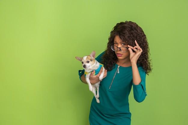 Pytanie, wątpliwości. afro-portret młodej kobiety w okularach na białym tle na zielonym tle studio. piękny model z małym pieskiem. pojęcie ludzkich emocji, wyraz twarzy, sprzedaż, reklama.