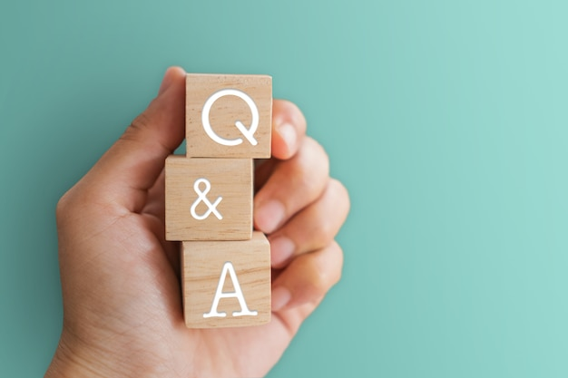 Q i a alfabet na drewnianym sześcianie w ręku. pytanie i odpowiedź znaczenie koncepcji.