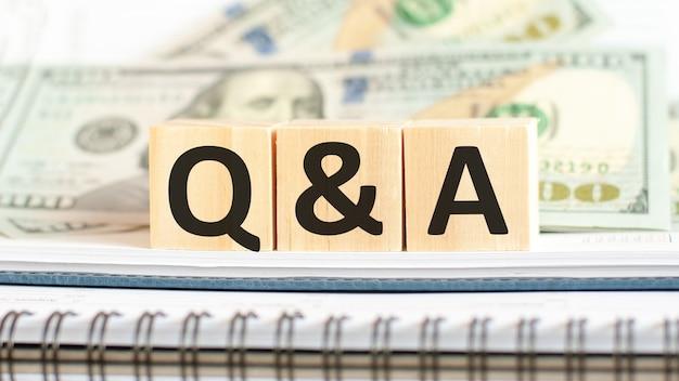 Q i skrót od pytania i odpowiedzi. koncepcja biznesowa na drewniane kostki i dolary