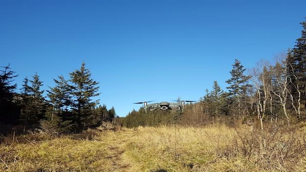 Quadkopter leci po błękitnym niebie na terenach górskich. uav. nowoczesna technologia . na dworze.