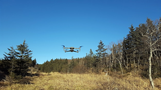 Quadkopter leci po błękitnym niebie na terenach górskich. uav. nowoczesna technologia .