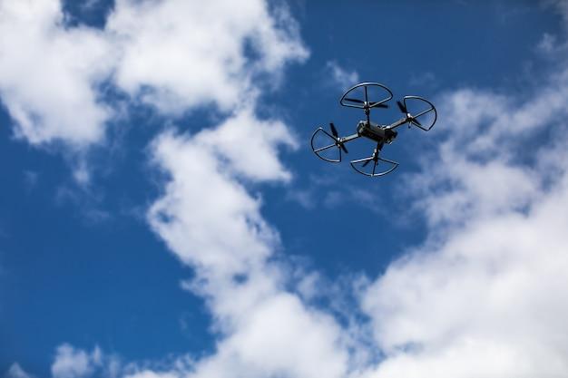 Quadrocopter na tle błękitnego nieba z białymi chmurami