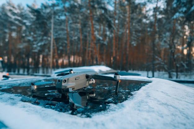 Quadrocopter stojący na dachu zaśnieżonego samochodu
