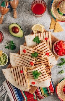 Quesadillas z grilla na desce iz salsą i guacamole na kamiennym tle. koncepcja kuchni meksykańskiej quesadilla wrap z kurczakiem i kukurydzą. widok z góry