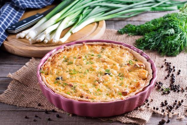 Quiche lub placek z francuskiego sera cebulowego posypane pietruszką, ze składnikami na desce do krojenia