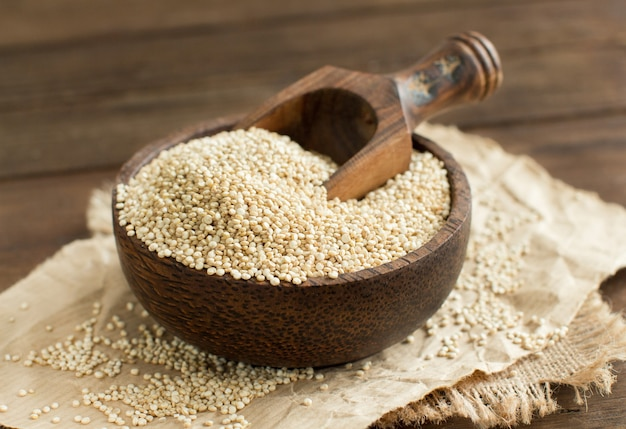 Quinoa biały w misce z drewnianą łyżką z bliska