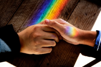 Ręce trzymają się razem ze światłami pryzmatycznymi