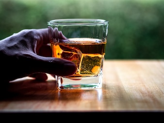 Ręka chwyta whisky szkło z natury tłem