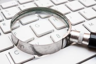 Ręka obiektyw na klawiaturze, internet rewizi pojęcie