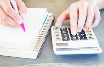 Ręka trzyma długopis i naciśnięcie przycisków kalkulatora
