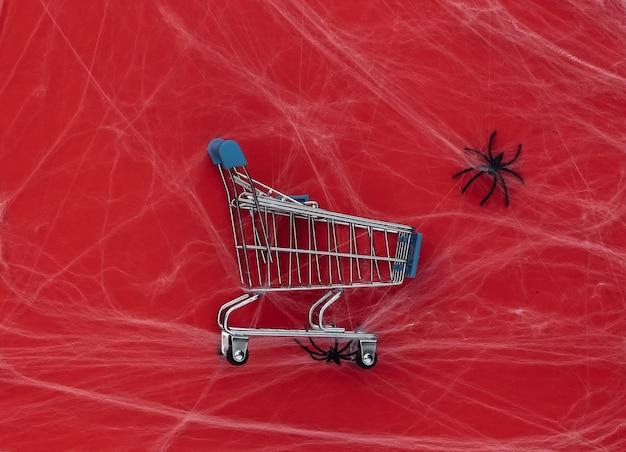 Rabaty halloween, zakupy. wózek w supermarkecie na czerwono z pajęczynami i pająkami. halloweenowa dekoracja