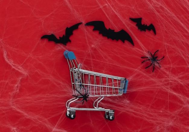 Rabaty halloween, zakupy. wózek w supermarkecie na czerwono z pajęczynami, nietoperzami i pająkami. halloweenowa dekoracja
