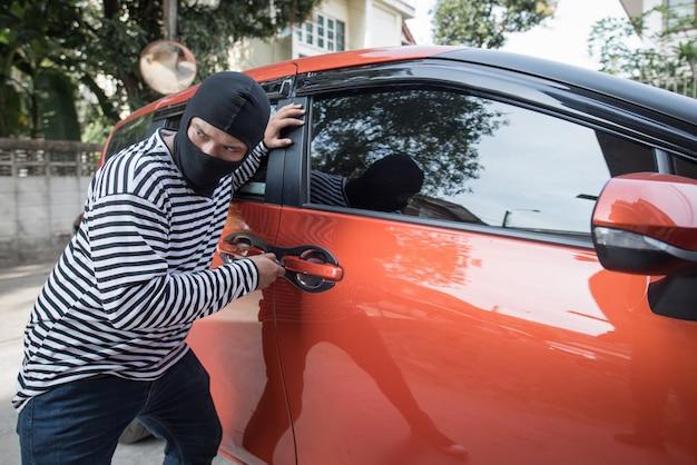 Rabuś i złodziej samochodów w masce otwiera drzwi samochodu i porywa samochód.