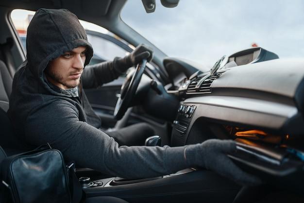 Rabuś samochodów przeszukuje schowek na rękawiczki, niebezpieczne hobby, kradzież.