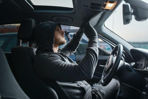 Rabuś samochodów przeszukuje wnętrze, niebezpieczne hobby, kradzież.