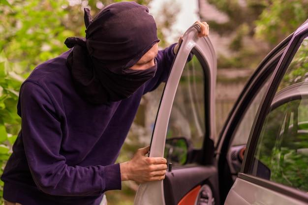 Rabuś stojący obok samochodu i próbujący ukraść rzeczy