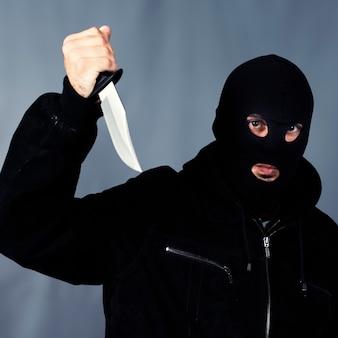 Rabuś z maską trzymając nóż