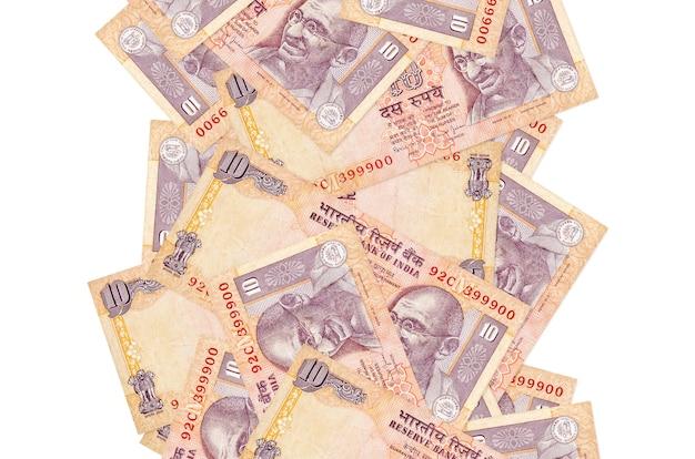 Rachunki 10 rupii indyjskich pływające w dół na białym tle
