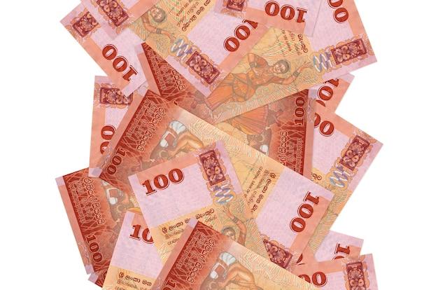 Rachunki 100 rupii lankijskich pływające w dół na białym tle