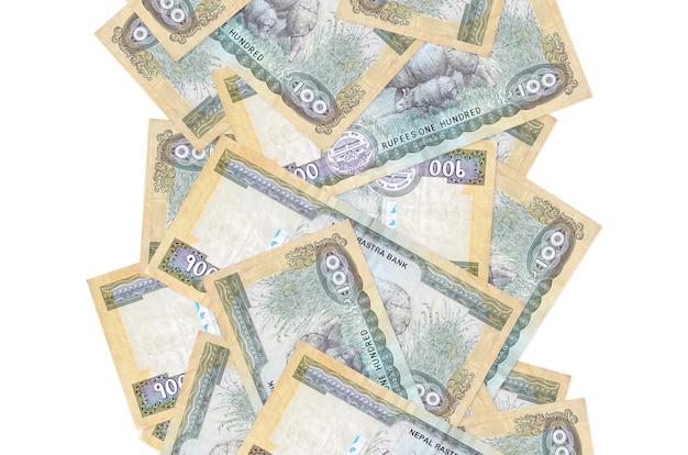 Rachunki 100 rupii nepalskich lecą w dół na białym tle. wiele banknotów spada z białą przestrzenią na kopię po lewej i prawej stronie