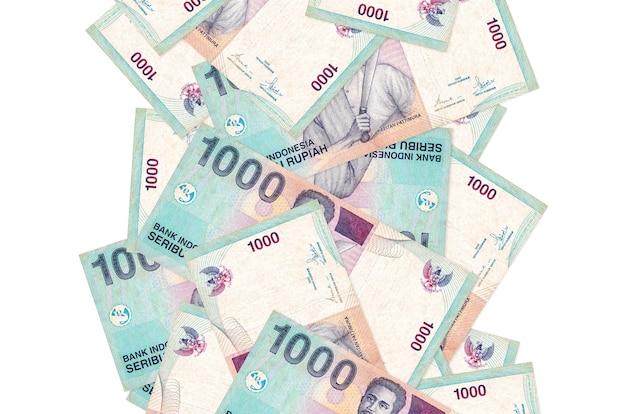 Rachunki 1000 rupii indonezyjskiej pływające w dół na białym tle. wiele banknotów spada z białą przestrzenią na kopię po lewej i prawej stronie