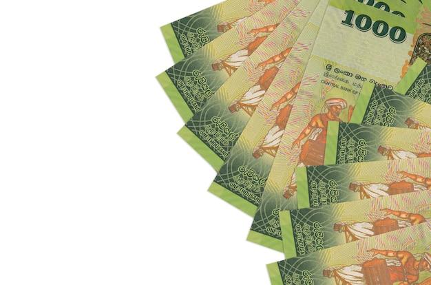 Rachunki 1000 rupii lankijskich leży na białym tle na białej ścianie z miejsca na kopię. . duża ilość bogactwa w walucie krajowej