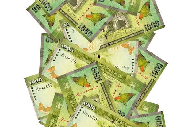 Rachunki 1000 rupii lankijskich pływające w dół na białym tle