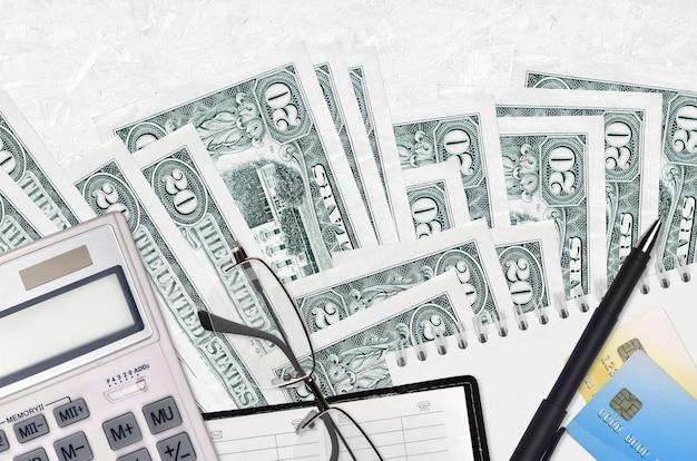 Rachunki 20 dolarów amerykańskich i kalkulator z okularami i długopisem.