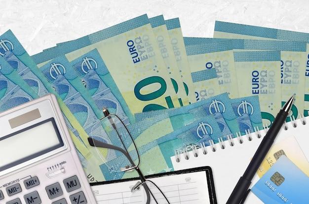 Rachunki 20 euro i kalkulator z okularami i długopisem. koncepcja sezonu płatności podatku lub rozwiązania inwestycyjne. planowanie finansowe lub dokumenty księgowe