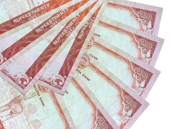 Rachunki 20 rupii nepalskich leżą na białym tle na białej ścianie z miejsca na kopię ułożone w kształcie wentylatora z bliska. koncepcja transakcji finansowych