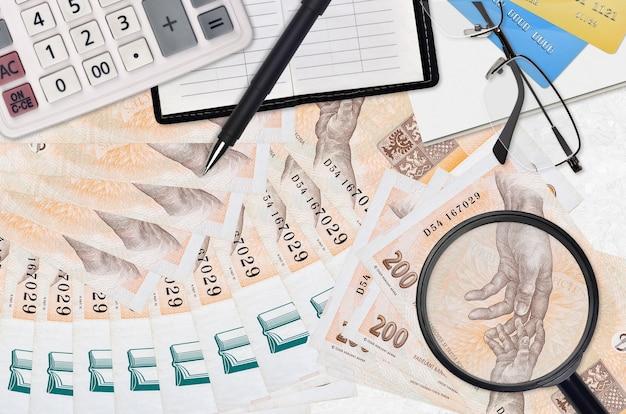 Rachunki 200 koron czeskich i kalkulator z okularami i długopisem. koncepcja sezonu płatności podatku lub rozwiązania inwestycyjne. poszukiwanie pracy z wysokimi zarobkami
