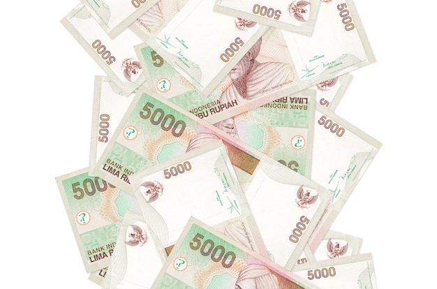 Rachunki 5000 rupii indonezyjskiej pływające w dół na białym tle. wiele banknotów spada z białą przestrzenią na kopię po lewej i prawej stronie
