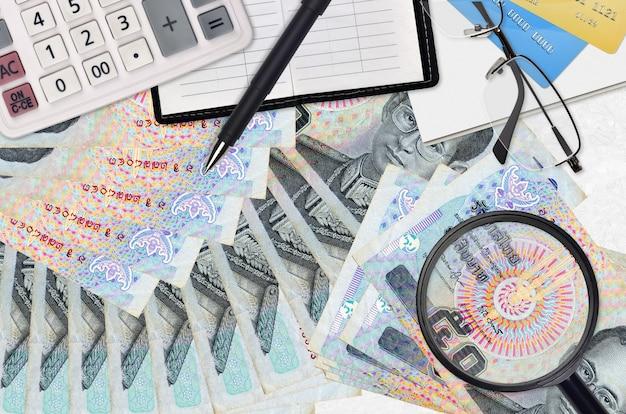 Rachunki bahta tajskiego i kalkulator z okularami i długopisem