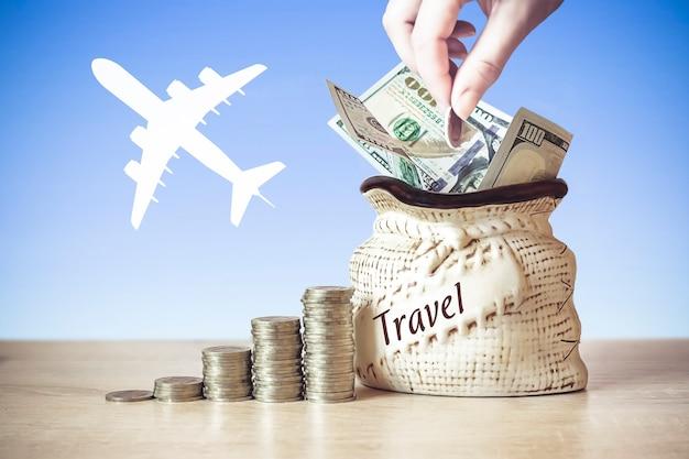 Rachunki dolarowe w torbie z monetami stos na stole rozmycie tła z sylwetką samolotu