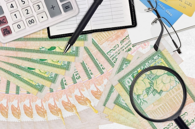 Rachunki rupii lankijskich i kalkulator z okularami i długopisem