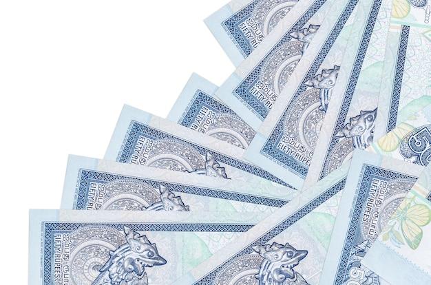 Rachunki rupii lankijskich leżą w innej kolejności na białym tle