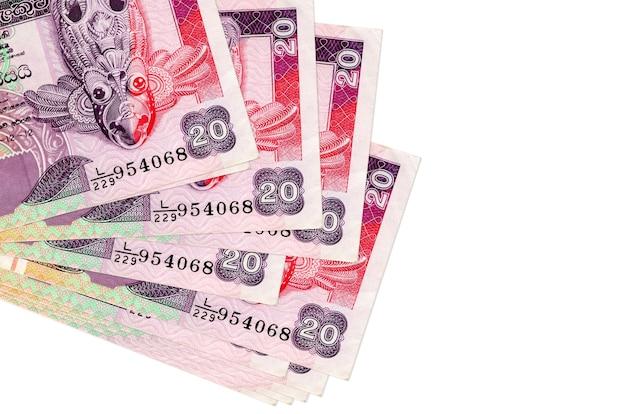 Rachunki rupii lankijskich leżą w małej wiązce lub paczce na białym tle