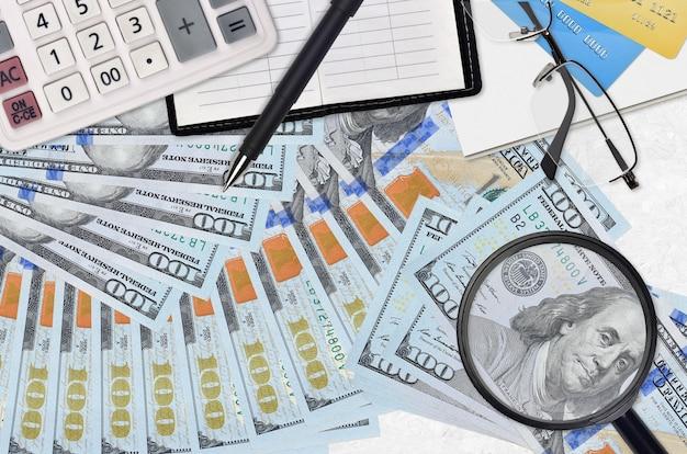 Rachunki w dolarach amerykańskich i kalkulator z okularami i długopisem