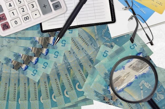 Rachunki w dolarach kanadyjskich i kalkulator z okularami i piórem